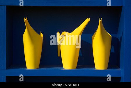 Three yellow plastic watering cans against a bright blue background - Stock Photo