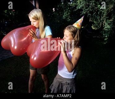 two girls blowing up red balloons preparing for birthday party - Stock Photo