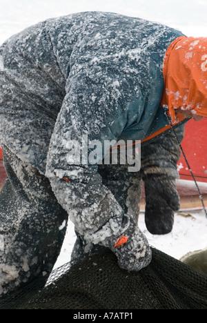 Smelt Fishing through the ice on a freezing cold winter day on Miramichi Bay New Brunswick - Stock Photo