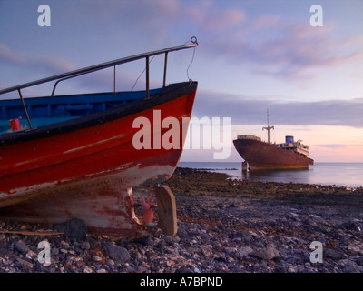 Rusting shipwreck lies in shallow water in rocky cove with abandoned red fishing boat in foreground on shingle beach - Stock Photo