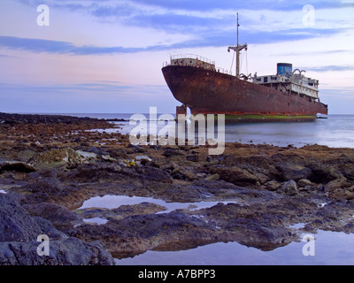 Rusting shipwreck lies in shallow water in volcanic rocky cove - Stock Photo
