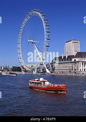 London red river Thames tour boat passing millennium eye Ferris wheel and the county hall & Shell building - Stock Photo