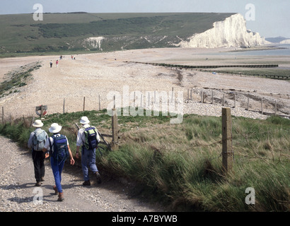 Seaford Head walkers on gravel track striding out towards River Cuckmere estuary with Seven Sisters white chalk - Stock Photo