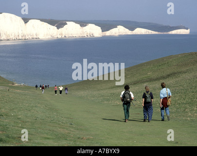Seaford Head walkers on grass downs with Seven Sisters white chalk cliffs beyond - Stock Photo