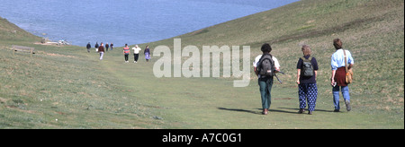 Seaford Head walkers on grass downs with sea beyond - Stock Photo