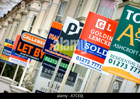 Estate agent for sale boards stacked up down a street. Picture by Jim Holden. - Stock Photo
