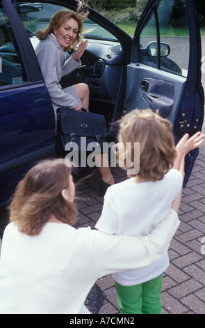 Mother waving goodbye to child as she gets into car - Stock Photo