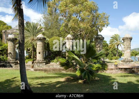 The restored 17th century boat house and sail loft pillars stand amid luxuriant green vegetation at Nelson's Dockyard, - Stock Photo