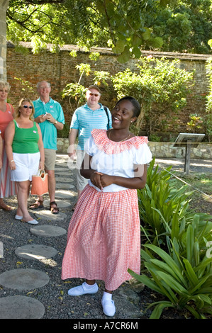A smiling female guide explains points of interest to tourists in a shady area of eighteenth-century Nelson's Dockyard, - Stock Photo