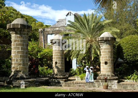Two local female guides in 17th century dresses stand by the boat house and sail loft pillars, Nelson's Dockyard, - Stock Photo