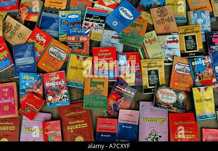 Selection of Burmese literature being sold at market Burma Myanmar - Stock Photo