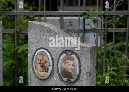 Two enameled portrait photos on headstone of children's grave in graveyard Almaty Kazakhstan - Stock Photo