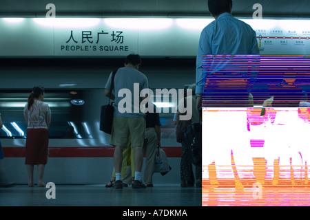 Asia China Shanghai Passengers wait on station platform to board Metro subway train at Peoples Square station - Stock Photo
