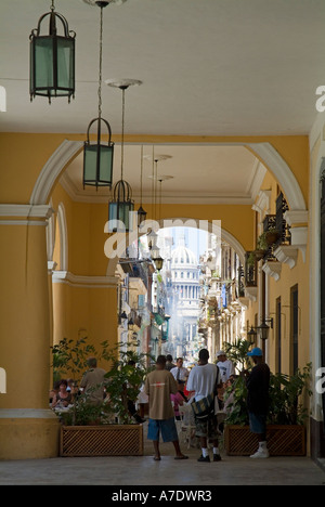 People under the walkway and the Taberna de la Muralla on Plaza Vieja in Havana, Cuba. - Stock Photo