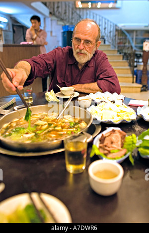 CHINA WUHAN Western tourist enjoying Mongolian hotpot meal with a variety of food and condiments at Wuhan restaurant - Stock Photo