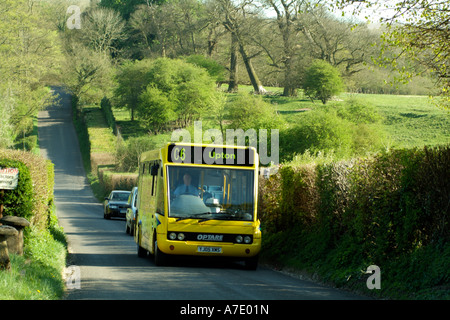Cango bus service. Single deck bus travelling along a country lane. Hampshire England UK - Stock Photo