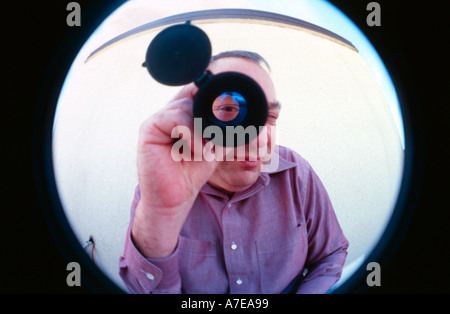 An Israeli engineer looking through an optical eyepiece device in Electro optic company in Israel - Stock Photo