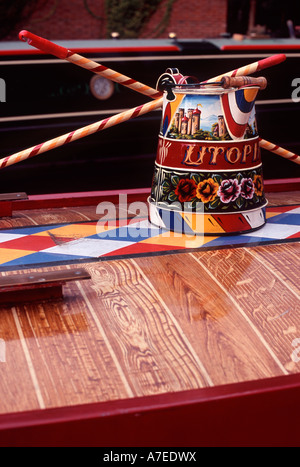Roses and castles: Traditional canalware and striped broom and mop handles on diamond patterned and scumbled narrowboat - Stock Photo