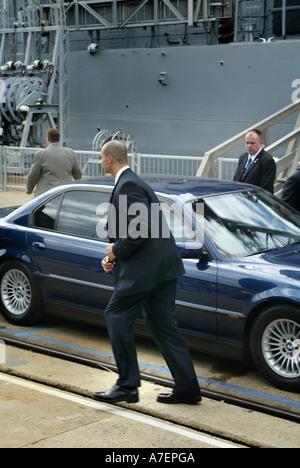 United States Political security staffer on duty with ear-piece and armored BMW car - Stock Photo