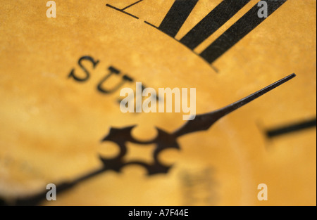 Close up detail of the minute hand indicating the time on the face of an old antique clock or watch - Stock Photo