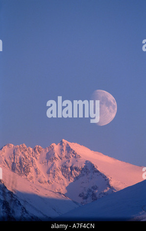 USA Alaska Chugach State Park Full moon rises over Chugach Range peaks lit by setting winter sun - Stock Photo
