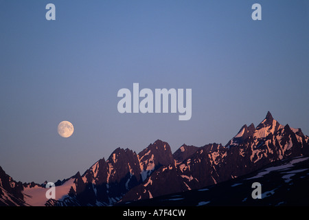 USA Alaska Chugach National Forest Full moon rises over Chugach Range peaks near Thompson Pass north of Valdez - Stock Photo