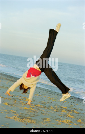 Young woman doing cart wheel on beach - Stock Photo