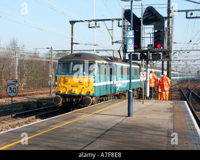 Essex main line railway with maintenance workers in high visibility safety clothing on platform - Stock Photo