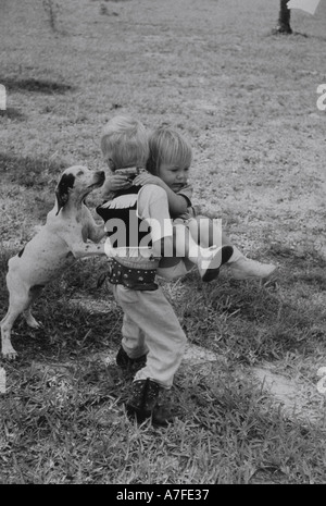 Big brother carries little sister to safety when dog frightens her - Stock Photo