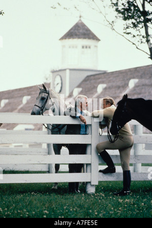Two men with horses talking over a white fence - Stock Photo