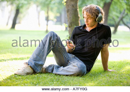 A teenage boy sitting in a park listening to music - Stock Photo