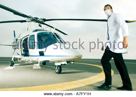 A doctor running towards a helicopter - Stock Photo