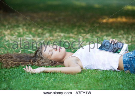 A teenage girl laying in a park - Stock Photo