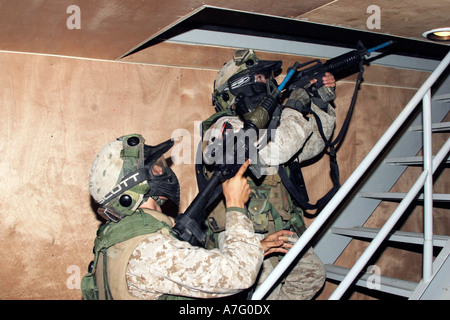 Infantry scouts go up a flight of stairs, moments away from a simunitions-round firefight inside a building. - Stock Photo