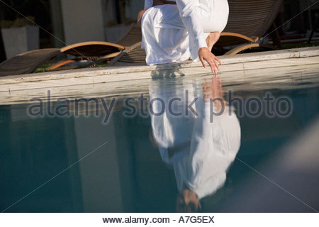 A woman testing the temperature of a swimming pool - Stock Photo