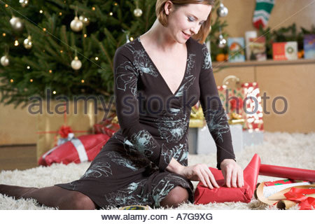 A woman wrapping Christmas presents - Stock Photo
