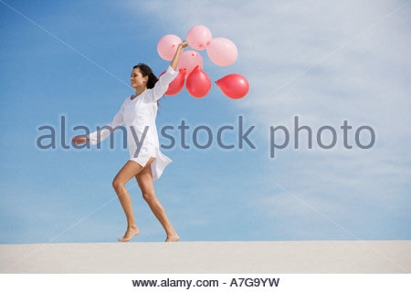 A woman walking in the desert holding a bunch of balloons - Stock Photo