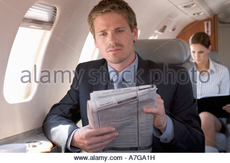 A businessman reading the paper on a plane - Stock Photo