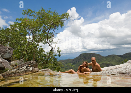 A tourist couple relax in a rock formation which create natural water pools in The Chapada dos Veadeiros National - Stock Photo