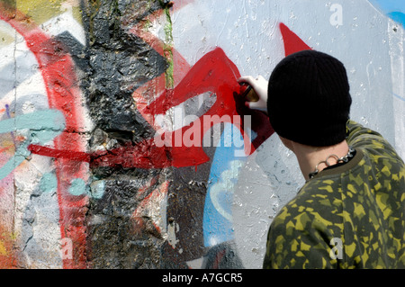 Young male sprays graffiti on a wall in Brighton, UK, Photo text 18th March 2006. - Stock Photo
