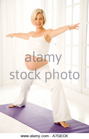 A pregnant woman practicing yoga - Stock Photo