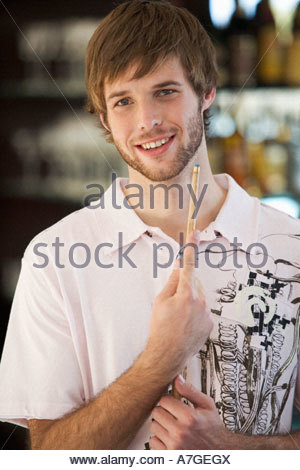 Portrait of a young man playing pool - Stock Photo