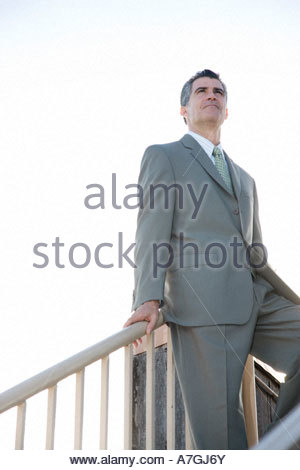 A businessman standing on the top of a flight of steps - Stock Photo