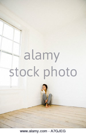A young woman sitting in the corner of an empty room - Stock Photo