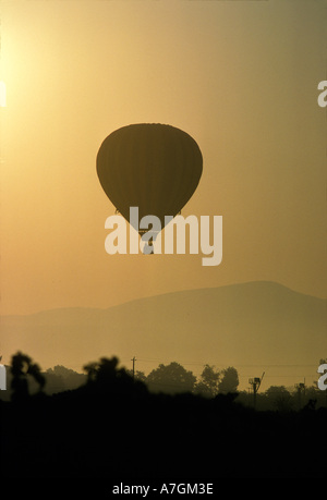 Hot air balloon lifting over Napa valley at sunrise. - Stock Photo