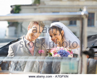 A bride and groom sitting in the wedding car - Stock Photo