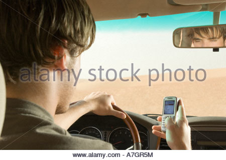 A young man using a mobile phone whilst driving - Stock Photo