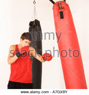 A young man training on a punch bag - Stock Photo