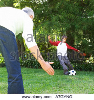 Father and son playing football in a garden - Stock Photo