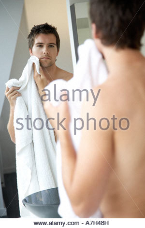 Young man drying his face with a towel - Stock Photo
